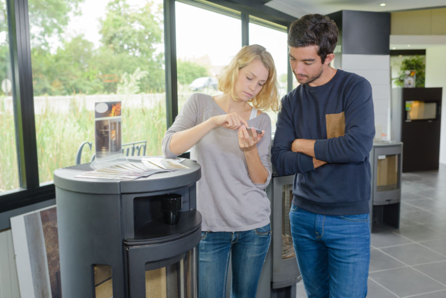 Un couple devant un poêle à bois avec une calculatrice en main